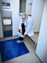 Cleanroom employee putting on shoe covers and using a sticky mat